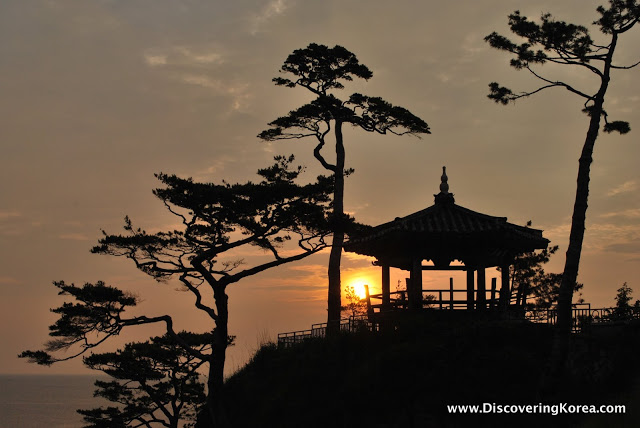 The sun rising behind a silhouette of a small gazebo and trees.
