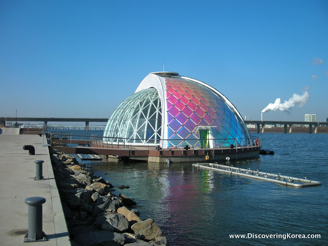 A glass dome floating stage on Yeouido island, on the water with the city behind it.